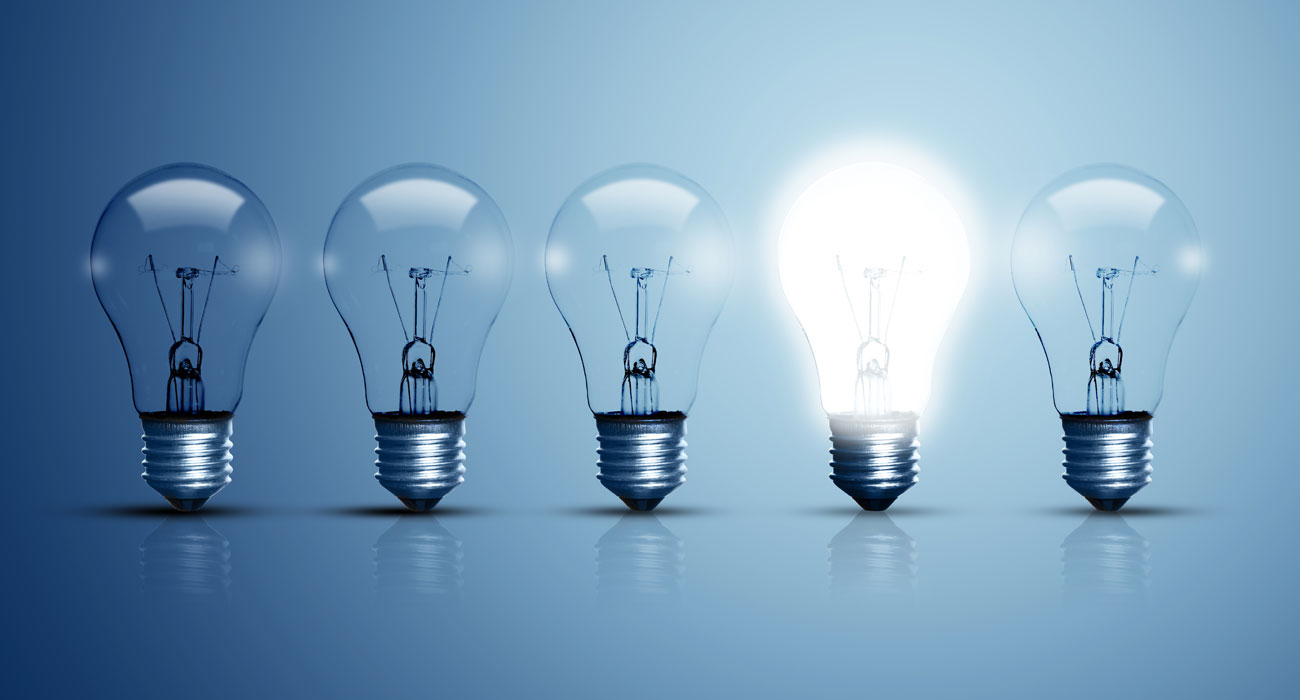 A row of five lightbulbs. The fourth lightbulb is shining brightly.